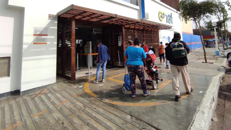 Foto de personas haciendo fila en exterior de empresa ENEL